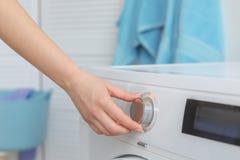 Jeune femme faisant la blanchisserie à la maison, images libres de droits