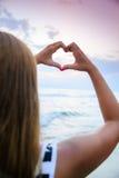 Jeune femme faisant la forme de coeur Images stock