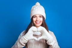 Jeune femme faisant la forme de coeur avec des mains Hiver d'amour Images stock