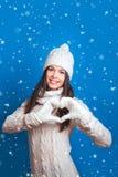 Jeune femme faisant la forme de coeur avec des mains Hiver d'amour Joli y Photos stock