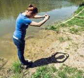 Jeune femme faisant la forme de coeur avec ses mains par le lac Image stock