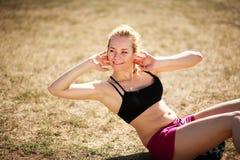 Jeune femme faisant la forme physique abdominale d'exercice extérieure photos stock