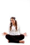 Jeune femme faisant la méditation avec la musique Image libre de droits