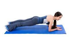 Jeune femme faisant la séance d'entraînement de planche de coude photographie stock