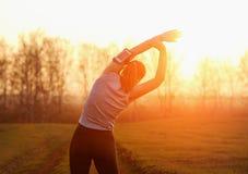 Jeune femme faisant la séance d'entraînement sur la route au coucher du soleil Image stock