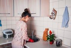 Jeune femme faisant la vaisselle dans la cuisine moderne photographie stock