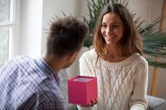 Jeune femme faisant le boîte-cadeau ouvert donnant actuel au mari Photos stock