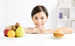 Jeune femme faisant le choix entre la nourriture saine et néfaste Image libre de droits
