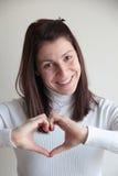 Jeune femme faisant le signe de coeur avec des mains Photographie stock libre de droits