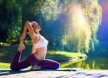 Jeune femme faisant le yoga dans le beau matin près du lac images libres de droits