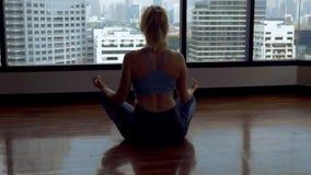 Jeune femme faisant le yoga dans une chambre près d'une grande fenêtre donnant sur les gratte-ciel banque de vidéos