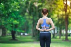 Jeune femme faisant le yoga en parc Photo stock