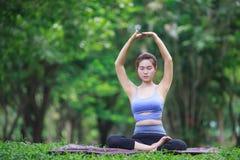 Jeune femme faisant le yoga en parc Photographie stock