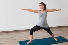 Jeune femme faisant le yoga prénatal dans la pose du guerrier deux image stock