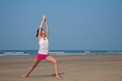 Jeune femme faisant le yoga sur la plage Photographie stock