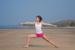 Jeune femme faisant le yoga sur la plage Images stock