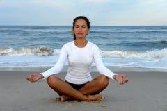 Jeune femme faisant le yoga sur la plage photo stock