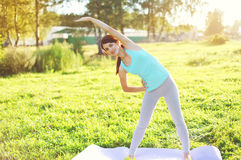 Jeune femme faisant le yoga étirant des exercices sur l'herbe Photographie stock