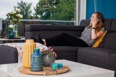 Jeune femme faisant un appel téléphonique sur le divan photo libre de droits