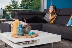 Jeune femme faisant un appel téléphonique sur le divan image stock