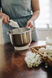 Jeune femme faisant un gâteau cuire au four utilisant un mélangeur images stock