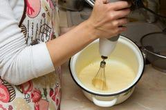 Jeune femme faisant un gâteau cuire au four utilisant un mélangeur, mousee dans la cuvette images stock