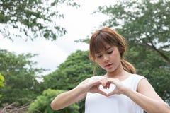 jeune femme faisant un geste de coeur avec ses doigts Fille asiatique Images stock