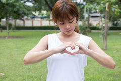 jeune femme faisant un geste de coeur avec ses doigts Fille asiatique Images libres de droits
