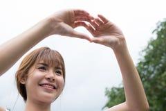 jeune femme faisant un geste de coeur avec ses doigts Fille asiatique Photographie stock libre de droits
