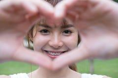 jeune femme faisant un geste de coeur avec ses doigts Fille asiatique Image stock