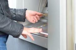 Jeune femme faisant un retrait d'opérations bancaires Photo stock