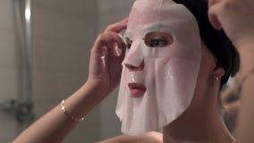 Jeune femme faisant une fin faciale de masque  clips vidéos
