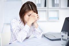 Jeune femme fatiguée d'affaires dans le bureau Photos libres de droits