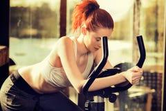 Jeune femme fatiguée faisant l'exercice sur la bicyclette à la maison photo stock