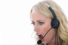 Jeune femme fâchée attirante d'affaires à l'aide d'un casque de téléphone Photographie stock libre de droits