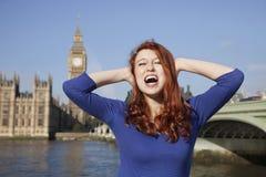 Jeune femme fâchée avec des mains sur les cris principaux contre la tour d'horloge de Big Ben, Londres, R-U Images stock