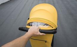 Jeune femme flânant un chariot extérieur Plan rapproché tiré des mains masculines avec la poignée jaune de poussette Poussée de m photo stock