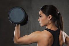 Jeune femme fléchissant des muscles avec des haltères dans le gymnase photographie stock