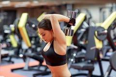 Jeune femme fléchissant des muscles avec l'haltère dans le gymnase photo libre de droits