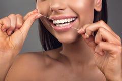 Jeune femme flossing ses dents avec plaisir Images stock