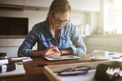 Jeune femme focalisée travaillant en ligne avec un comprimé de maison images libres de droits