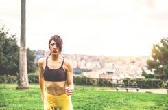 Jeune femme fol?tre courant dans la nature en parc ext?rieur - sportive pulsant dans la ville images stock