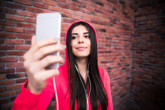 Jeune femme folâtre heureuse regardant sur le smartphone Photo libre de droits