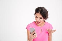 Jeune femme folle fâchée criant et à l'aide du téléphone portable Photographie stock libre de droits
