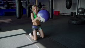 Jeune femme forte avec le corps parfait de forme physique dans les vêtements de sport s'exerçant avec le medicine-ball au gymnase banque de vidéos