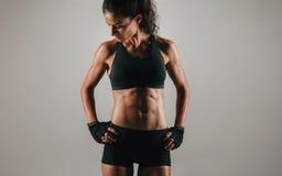 Jeune femme forte d'ajustement montrant son ABS Photographie stock libre de droits