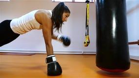 Jeune femme forte de cheveux foncés faisant des exercices dans le gymnase banque de vidéos