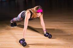 Jeune femme forte faisant l'exercice de pousées avec des haltères Modèle de forme physique faisant la formation intense dans le g photo stock
