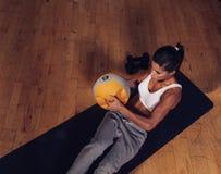 Jeune femme forte faisant la séance d'entraînement de noyau photo stock