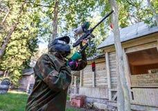 Jeune femme fraîche avec l'arme à feu de peinture jouant le jeu de paintball photo libre de droits